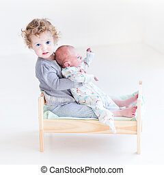 Funny toddler girl playing with her newborn baby brother in a to