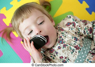 Funny toddler girl talking mobile cell phone