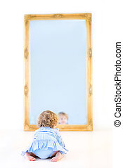 Funny toddler girl with beautiful curly hair wearing a blue dres