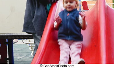 Funny toddler slides down and pouts