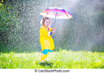 Funny toddler with umbrella playing in the rain - Funny cute...
