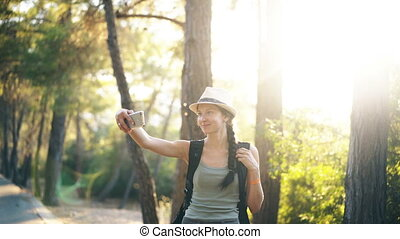 Funny tourist girl in hat taking selfie photos with...