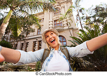 tourist taking selfie in front of historical building