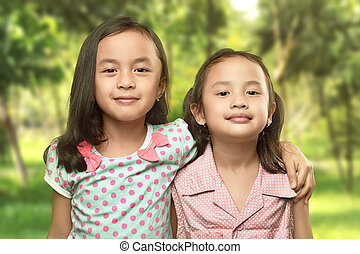 Funny two little sisters standing and hugging