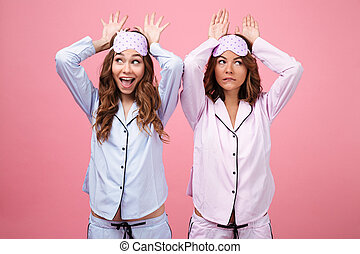 Funny two women friends in pajamas isolated over pink...