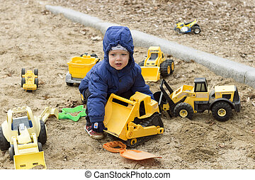Funny two years toddler playing with a big yellow toy cars on the sand. Spring or autumn photo.