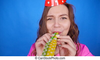 Funny woman celebrating birthday and hooting with horn