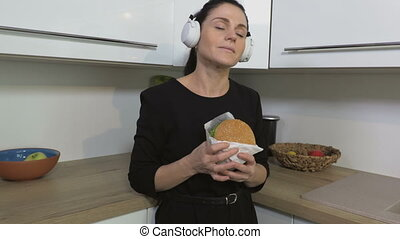 Funny woman dancing at kitchen wearing headphones and starting eating burger