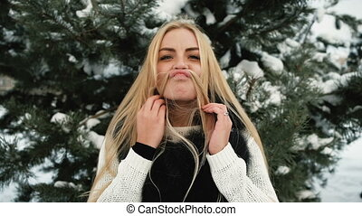 Funny woman fools around in pine winter snowy forest outdoors
