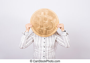Funny woman holding a golden bitcoin. Virtual money, crypto currency and blockchain concept