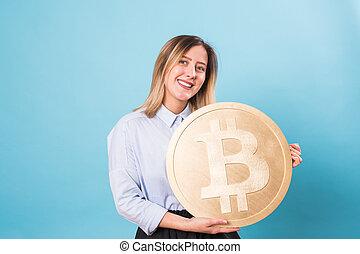 Funny woman holding a Golden Bitcoin. virtual money.