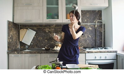 Funny woman housewife cook dance with big ladle while cooking in modern kitchen at home indoors