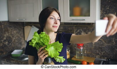 Funny woman housewife shoot selfie with green salad while cooking in the kitchen at home indoors