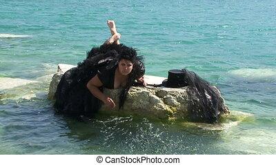 Funny Woman In Black Splashing Water In Lake