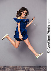 Funny woman in dress listening music and jumping