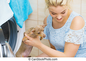 Funny woman putting little dog into washing machine
