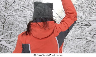 funny woman running by snow park touching the tree branch, snow falling, winter fun