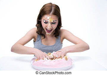 Funny woman sitting at the table with cake