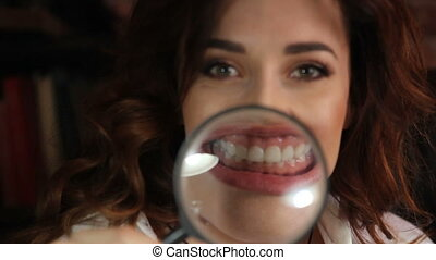 funny brunette woman smiling and show teeth through a magnifying glass