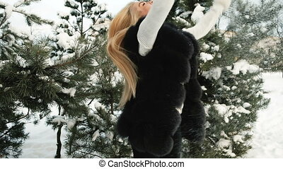 Funny woman throw snow up in pine winter snowy forest outdoors.