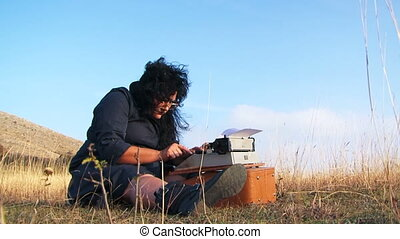 Funny Woman Typing On Vintage Typewriter Sitting On The Ground At Nature