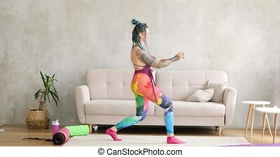 Funny woman with braided hairs is doing lunges at home, sport fitness concept.