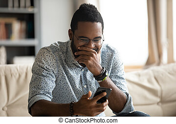 Funny young african ethnicity guy looking at cellphone screen.