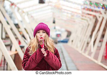 Funny young blonde woman in red knitted hat posing with candy cane at the street