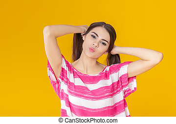 funny young brunette woman fooling around on yellow background.