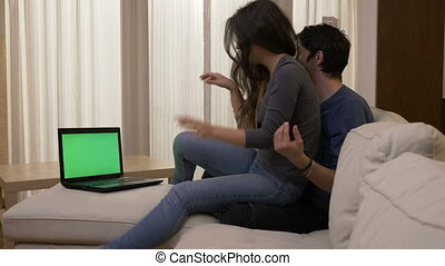 Funny young couple hugging and fooling around at home on a white sofa while watching a movie on the laptop with green screen kissing and showing affection