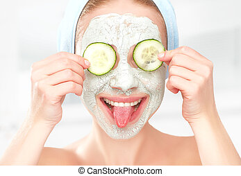 Funny young girl with a mask for skin face and cucumbers on...