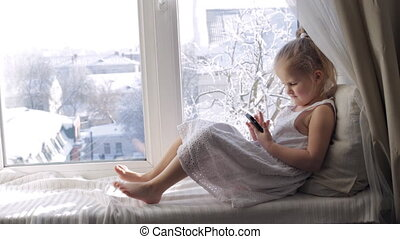Funny young girl with smartphone on a window sill. Sunny winter morning