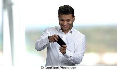 Funny young man addicted to play mobile game. Enthusiastic Indian man playing game on phone. People, modern technology and fun.