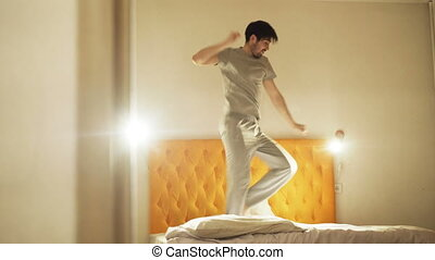 Funny young man dancing on bed in the evening before sleeping