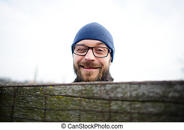 Funny young man with glasses and a beard looks out from behind the fence. He