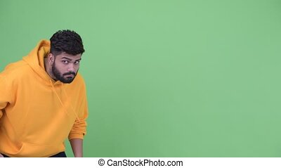 Funny young overweight bearded Indian man escaping - Studio...