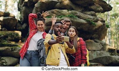 Funny young people happy friends are taking selfie in wood...
