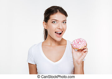 Funny young woman eating tasty donut on white background