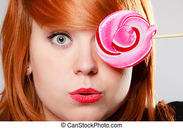 Funny young woman holding candy. Redhair girl with pink...