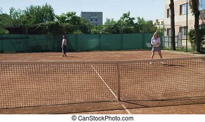 Funny young women playing doubles at a tennis court
