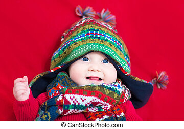 Funyn baby girl in a colorful knitted hat and scarf on a red bla