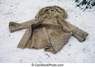 Fur coat abandoned on the snow