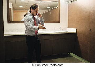 furieux, homme affaires, crier, sur, téléphone portable, dans, bureau, toilettes