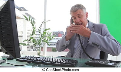 Furious businessman ending a call in an office
