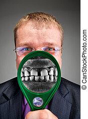 Furious businessman smiling through magnifier