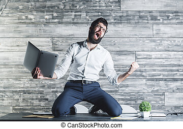 Stress concept - Furious businessman with laptop sitting on ...