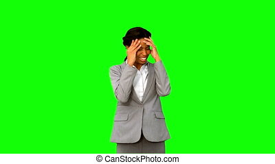Furious businesswoman holding her head on green screen in...