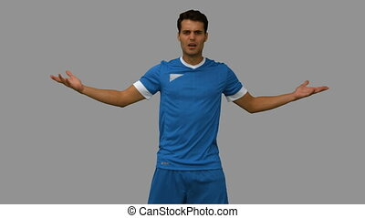 Furious football player gesturing on grey screen in slow...