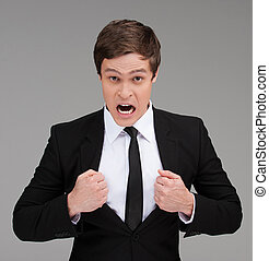 Furious man. Furious young businessman with open mouth grabbing his suit with both hands and looking at camera while isolated on grey