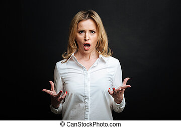 Furious mature woman yelling in the black colored studio